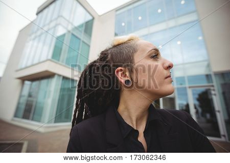 Close-up of businesswoman standing in office campus