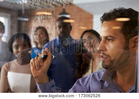 Businessman Writing Ideas On Glass Screen During Meeting