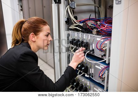 Technician examining server in server room