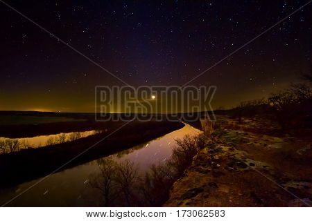 Nightscape of a bluff in the Lake of the Ozarks in Missouri overlooking the Osage River. The planet Uranus is glowing as a few clouds goes in front of it.
