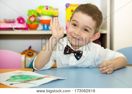 Adorable child boy draws a brush and paints in nursery room. Kid in kindergarten in Montessori preschool class.