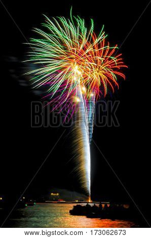 Colorful fireworks shot off in the night sky over the water