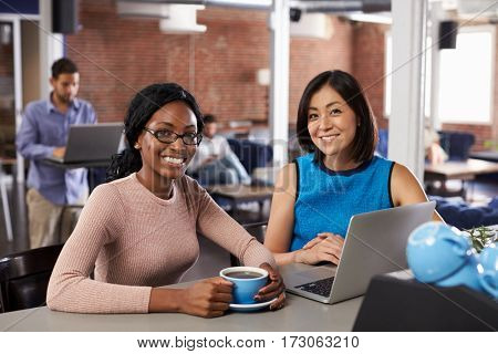 Two Businesswomen Have Informal Meeting In Office Coffee Bar