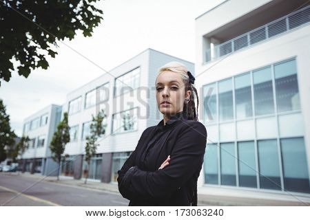 Portrait of businesswoman standing with arms crossed in office campus