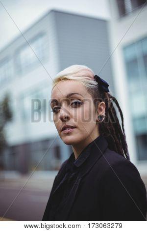 Portrait of confident businesswoman standing in office campus