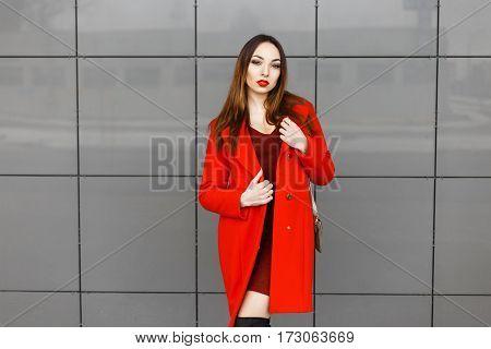 Beautiful Stylish Woman In A Fashionable Red Coat Posing Near A Gray Wall