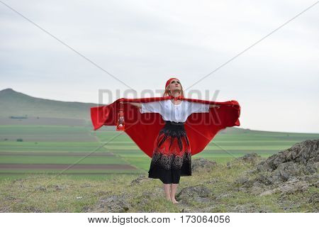 Beautiful Blonde Woman With Red Cloak Standing Barefoot In The Wind On The Edge Of A Mountain In The