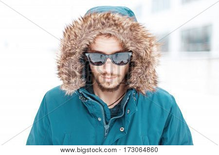 Handsome Man In Warm Winter Jacket With Fur Hood And Sunglasses.