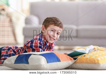 Little boy reading book on floor with pillows indoors