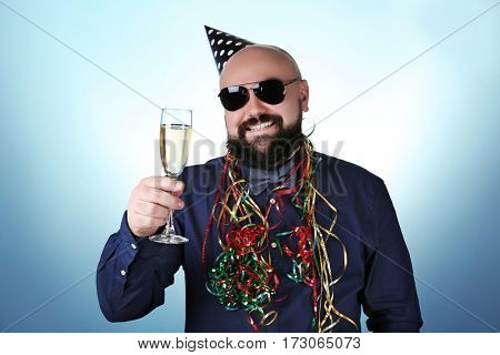 Funny fat man with birthday hat and glass of champagne on color background