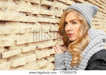 Young beautiful woman standing near brick wall background