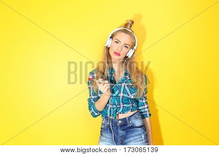 Young beautiful woman with headphones on yellow background