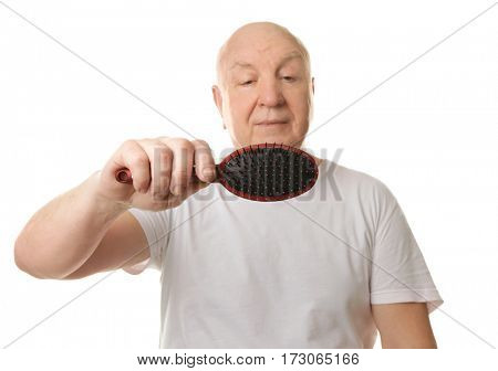 Bald senior man with hair brush on white background