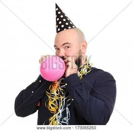 Funny fat man with birthday decor inflating balloon on white background