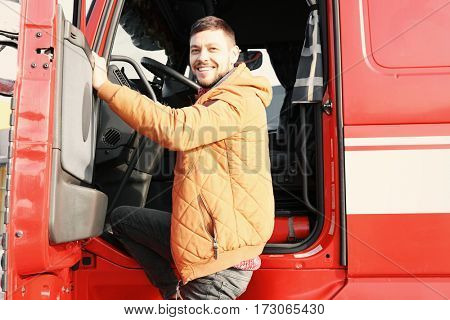 Handsome driver near big modern truck outdoors