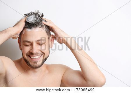 Young handsome man washing hair on white  background