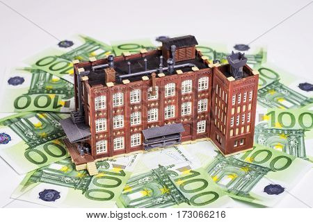Factory building is surrounded by euro banknotes.