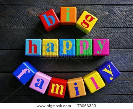 Colorful cubes with text BIG HAPPY FAMILY on wooden background
