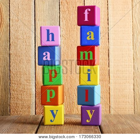 Colorful cubes with text HAPPY FAMILY on wooden background