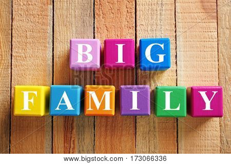 Colorful cubes with text BIG FAMILY on wooden background