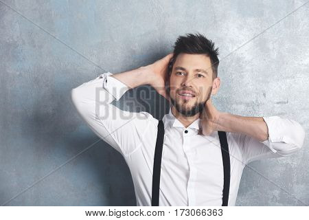 Handsome young man posing on gray background