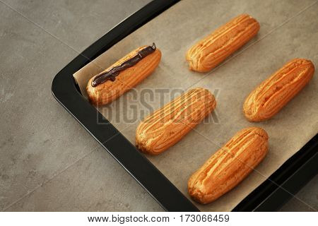 Delicious homemade eclairs with chocolate on baking tray