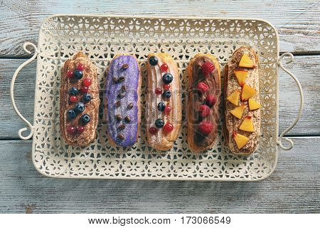 Delicious colourful eclairs with berries and fruit on tray