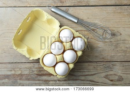 Raw eggs and whisk on wooden background