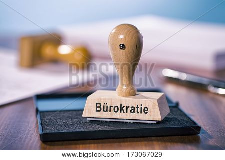 A stamp with the inscription bureaucracy stands on a desk.