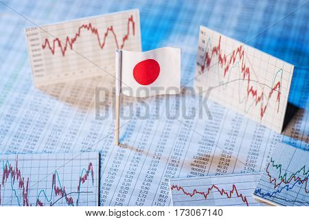 Japanese flag with rate tables and graphs for economic development.