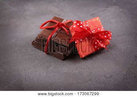 Chocolate pieces with present on grey background