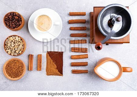 Fresh coffee with ingredients and accessories on grey background