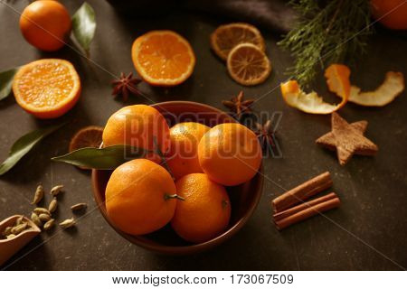 Composition of tangerine in plate on gray table