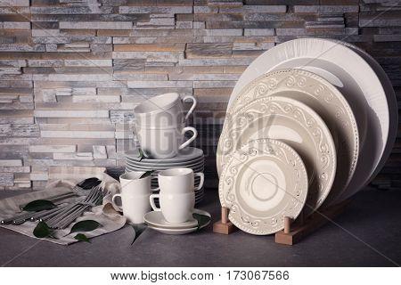 Set of rustic dinnerware on light brick background