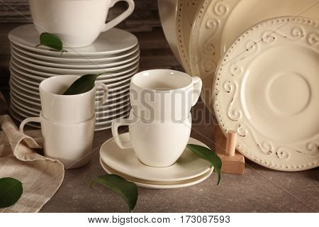 Composition with rustic dinnerware and green leaves
