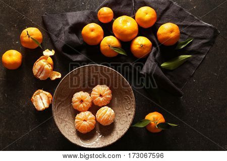 Peeled tangerine in plate on gray table