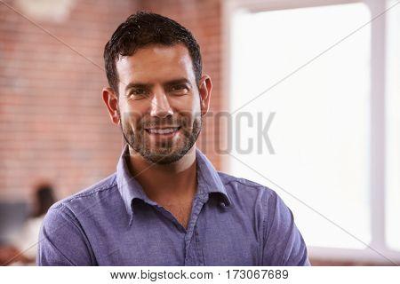 Portrait Of Businessman In Office Standing By Window