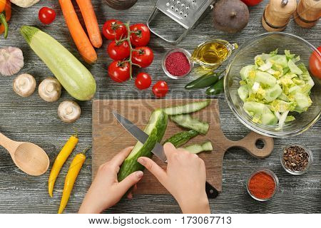 Female hands peeling cucumber at table, top view