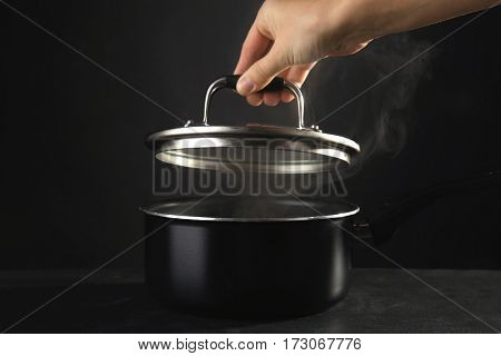 Human hand removing cover from saucepan with hot liquid, on dark background