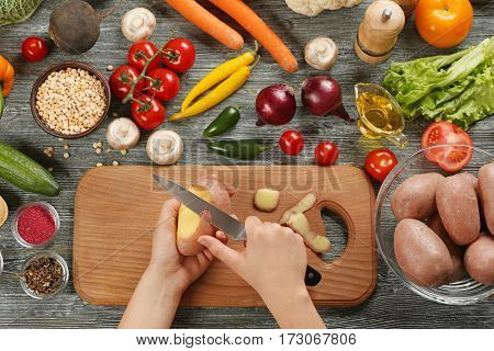 Female hands peeling potato at table, top view