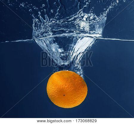Fresh juicy orange falling in water on dark background