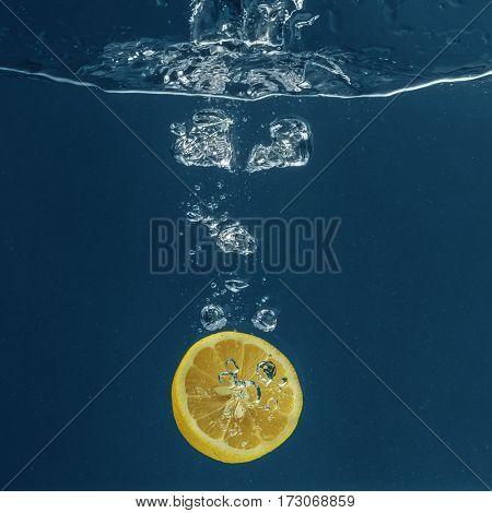 Half of fresh lemon falling in water on dark background