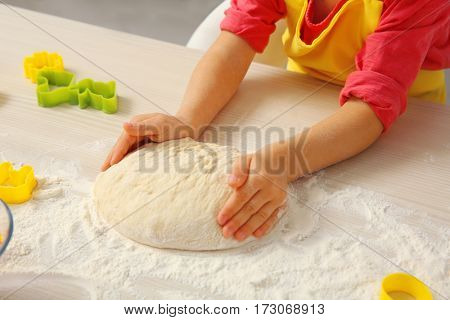 Little girl making dough for Easter cookies, closeup