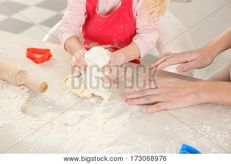 Young mother with daughter making biscuits on table