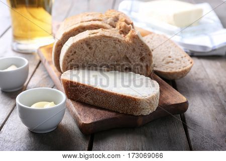 Wooden cutting board with sliced loaf of beer bread and butter on table