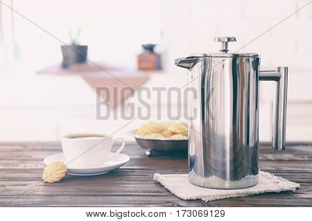 New coffee maker and cup of fresh drink with cookies on kitchen table