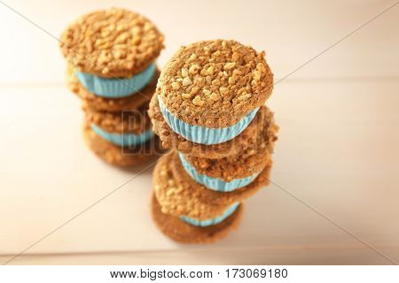 Tasty kiwi ice cream cookie sandwiches on wooden table