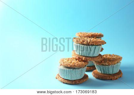 Pile of tasty kiwi ice cream cookie sandwiches on blue background