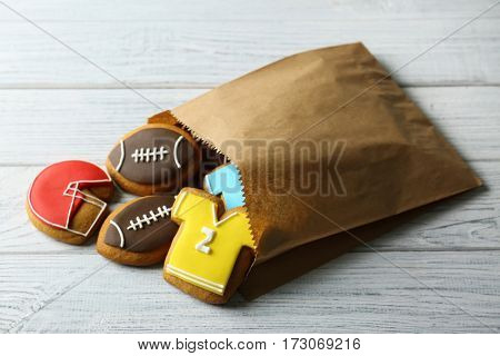 Paper bag with creative cookies decorated in football style on wooden background