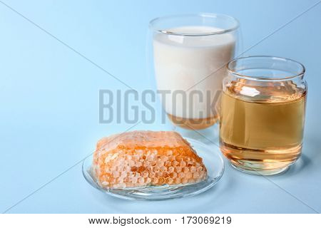 Composition with milk, honey and honeycomb on blue background